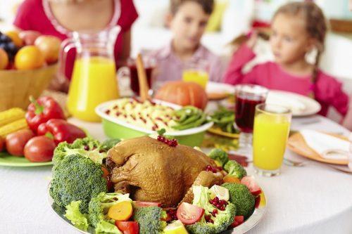 crianças ao fundo com uma mesa saudável contendo um peru, brócolis e outras verduras